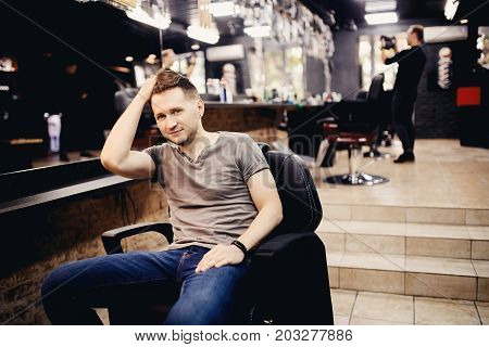 Man fixes his hair in a hairdresser's barbershop.