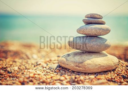 Stones pyramid on pebble beach symbolizing stability, zen, harmony, balance. Tropical sea beach. Vacation concept