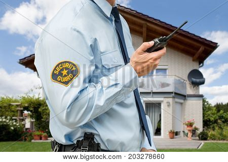 Close-up Of Security Guard Standing In Front Of Their House Holding Walkie Talkie