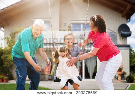 Happy Grandparents Looking At Their Grandchildren Playing On Swing In Front Of Their House