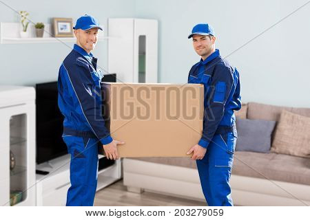 Two Young Smiling Movers In Uniform Delivering Cardboard Boxes In Living Room