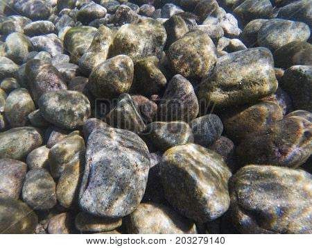 Seashore pebbles underwater photo texture. Seaside beach with big stones. Marine pebbles undersea texture. Beach stones background. Pebbles in seawater under sunlight. Tropical island shore
