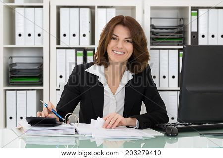 Portrait Of A Happy Accountant Woman Calculating Invoice