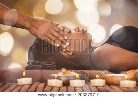 Young African Woman Receiving Forehead Massage By Male Therapist