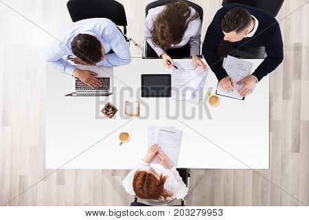 High Angle View Of Businesspeople Interviewing Female Applicant In Office