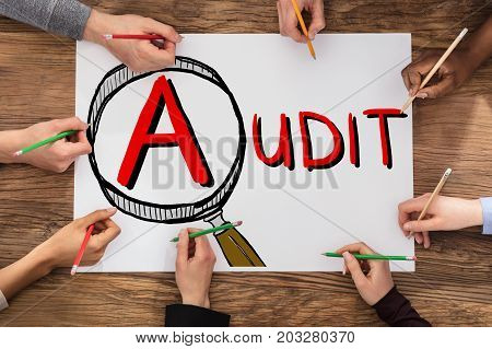 People Drawing Audit And Fraud Investigation Concept On Paper