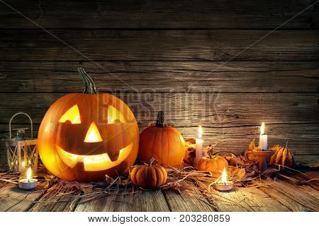 Halloween Pumpkins And Four Candles On Wooden