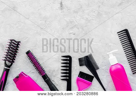 pink combs, brushes and spray for hairdresser work set on stone desk background top view mockup