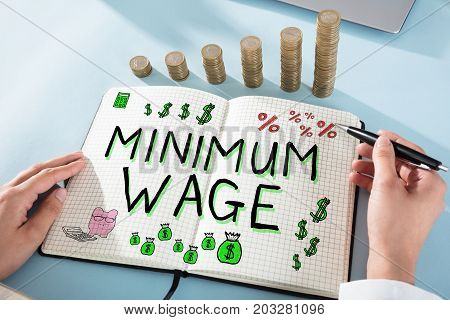 Woman Drawing Minimum Wage Words In Notepad