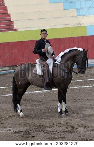 June 18 2017 Pujili Ecuador: a horseback toreador called 'rejoneador' during the national anthem played from loudspeakers before the show