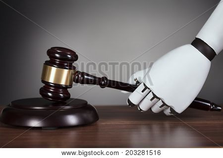 Close-up Of Robot's Hand Hitting Gavel At Wooden Desk