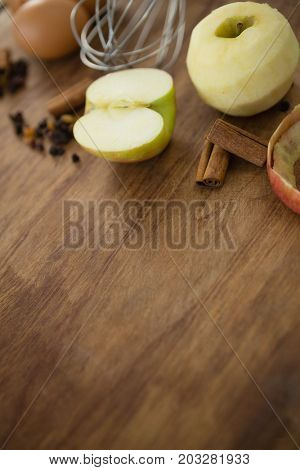 Granny smith apple with spices on wooden table