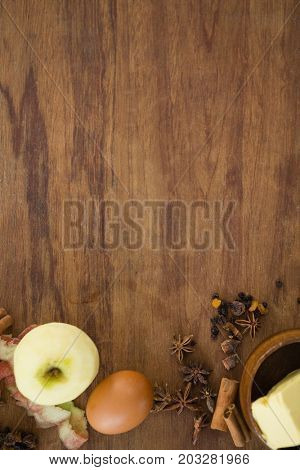 Directly above shot of granny smith apple with egg and spices on wooden table