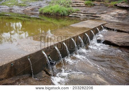 The construction of a small weir to slow down and store water on the top of the mountain