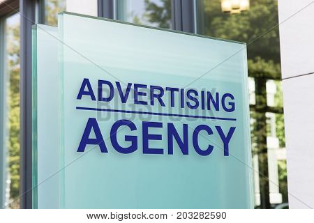 Closeup of advertising agency sign on glass board outside building in city