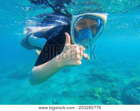 Snorkeling woman shows thumb. Snorkeling girl in full-face snorkeling mask. Diving in shallow sea. Snorkel girl undersea. Seashore underwater photo. Seaside fun activity. Water sport in tropical sea