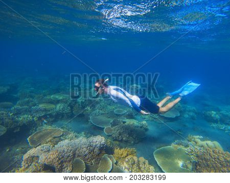 Young man swims underwater. Male snorkel in tropical lagoon undersea photo. Snorkeling in coral reef. Summer holiday activity. Water sport in open sea. Exploring tropical coral reef. Man on vacation
