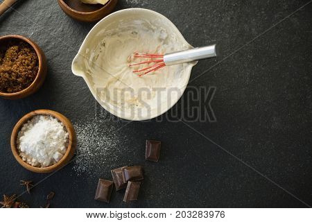 Directly above shot of batter in bowl by ingredients on table