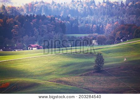Iew Of Beautiful Mountain Rural Landscape In The Alps With Village In The Background