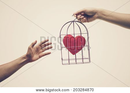 Female hands giving a bird cage with a red heart inside to a man