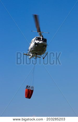 Helicopter with a Bambi bucket filled with water to fight a forest fire.