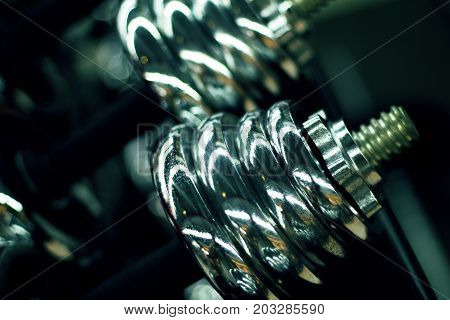 Dumbbells in gym closeup photo. Shiny metallic dumbbells or barbell weights. Metallic weight size for bar. Bodybuilding or fitness club banner template. Wellness health concept. Strong body training
