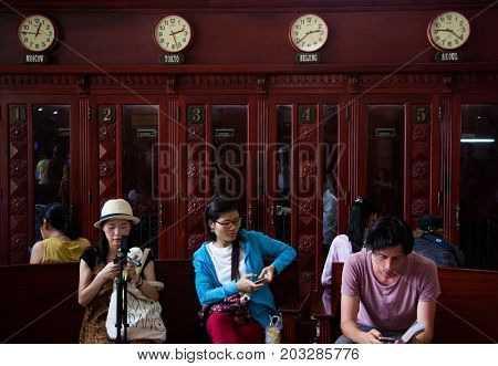 HO CHI MINH CITY (SAIGON), VIETNAM - JULY 2017 : tourists inside the central post office in neoclassical architectural style, designed and constructed by the famous architect Gustave Eiffel.