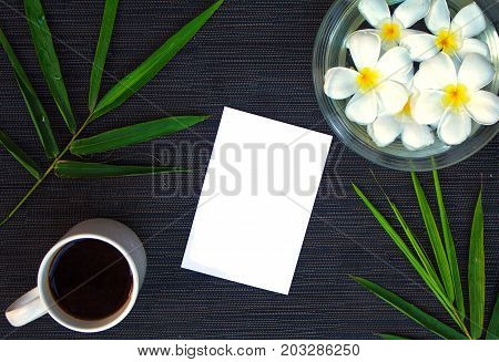 Bamboo leaf on rustic wood. Asian zen background. Blank paper in bamboo leaf and frangipani flower. Plumeria hand bath. Tropical flat lay. Spa beauty banner. Exotic island vacation. Travel card mockup