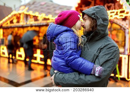 Adorable little girl and her father having wonderful time on traditional Christmas market. Parent and child enjoying themselves near Christmas stands decorated with lights and baubles.