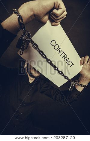 Stress at work no freedom pursuit of money concept. Scared man with chained hands holding contract studio shot on dark grunge background