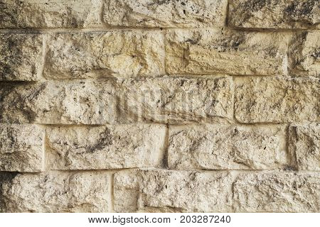 Yellow natural stone brick wall photo texture. Rough pale stone bricks surface design. Masonry wall made of big block. Rustic stone texture. Natural stone brickwork. Decorative exterior of old house