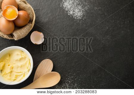Overhead view of butter by eggs in bowl on table