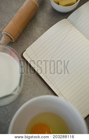 Overhead view of ingredients by open book on table