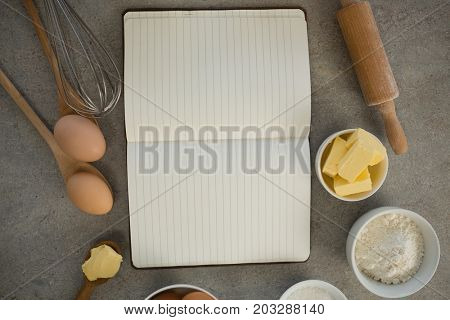 Overhead view of ingredients amidst open cookbook on table