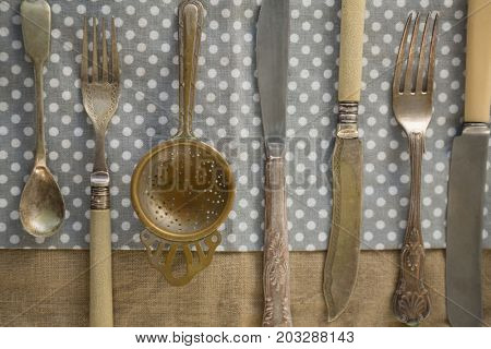 Directly above shot of cutlery arranged side by side on napkin