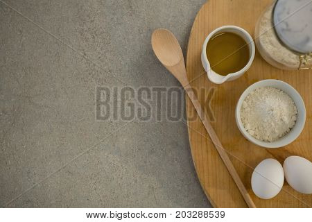Flour and oil with eggs on cutting board at table