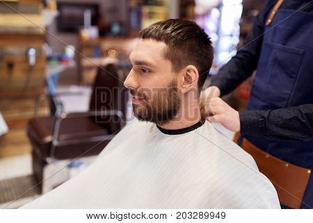grooming, hairdressing and people concept - hairdresser or barber and man in cape with beard at barbershop