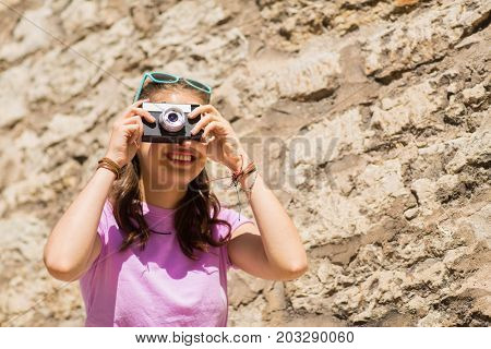 lifestyle, photography and people concept - happy smiling teenage girl or young woman with vintage camera outdoors
