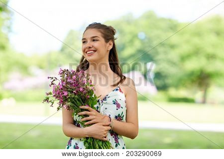 people, leisure and lifestyle concept - happy smiling young woman with flowers in summer park