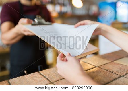 small business, people and service concept - bartender showing menu to customer at bar or coffee shop