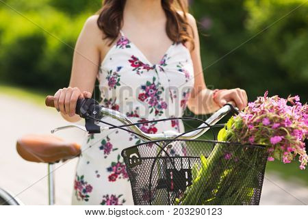 people, leisure and lifestyle concept - close up of young woman wearing summer dress with fixie bicycle and wild flowers in vintage basket at park