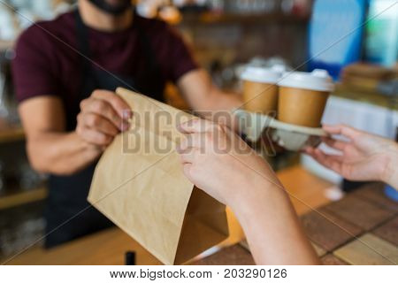 small business, people and service concept - man or bartender serving customer at coffee shop