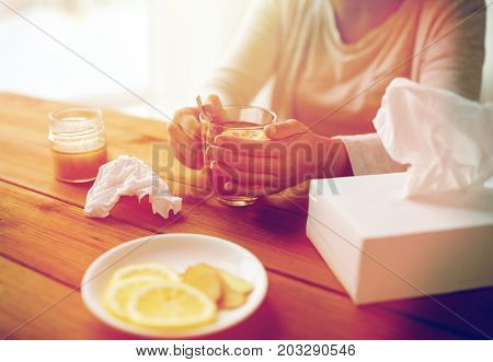 health, traditional medicine and ethnoscience concept - ill woman drinking tea with lemon and honey and paper wipes box on wooden table