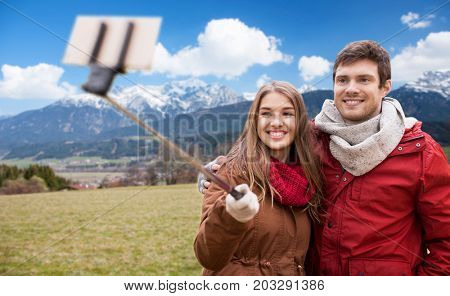 tourism, travel and people concept - happy smiling couple taking picture by smartphone selfie stick over alps mountains background