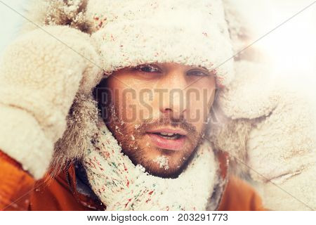 people, season and leisure concept - face of man in winter clothes outdoors