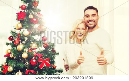 family, x-mas, winter holidays and people concept - happy couple showing thumbs up with christmas tree at home