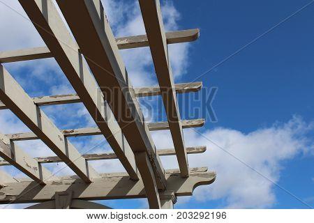Looking up at sky through slats of a pergola, close view