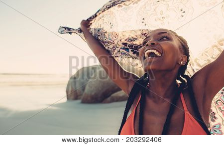 Beautiful woman laughing on the beach with scarf. Young black female with scarf flying on seashore.