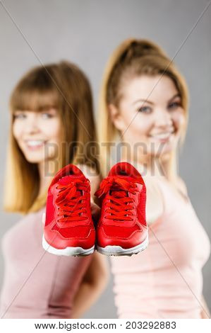 Two Women Presenting Sportswear Trainers Shoes