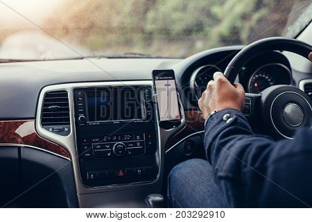 Man driving car with mobile navigation system. Male using mobile phone with map gps navigation in the car.